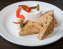 Škvarková pomazánka s cibulkami, okurky cornichons, cibulový chléb
