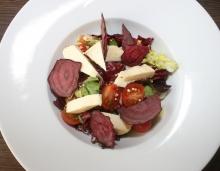 Směs trhaných listových salátů s cherry rajčaty, vlašskými ořechy, pohankou, nakládaným sýrem z farmy Menšík a s řepnými chipsy
